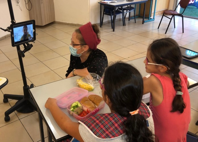 children eating together with a friend on a computer screen
