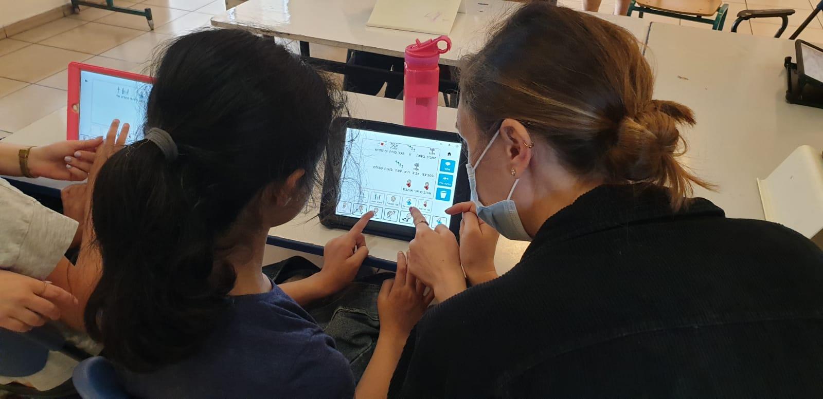 ילדה וסייעת עובדות עם תוכנת הגריד על משימה כיתתית